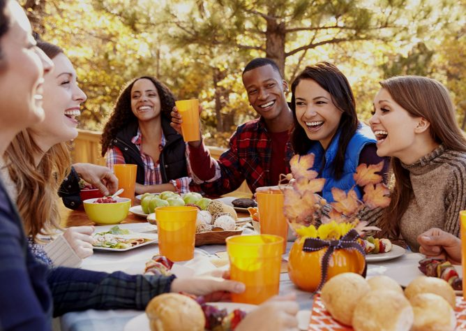 Friends gathered around a table for a Friendsgiving meal.