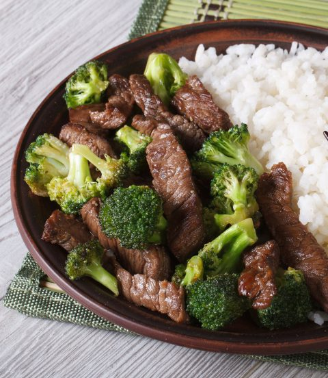 Beef and broccoli stir fry in a bowl with chopsticks.