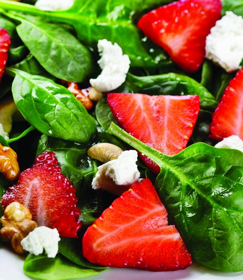 Simple superfood salad with spinach, strawberries, walnuts and feta cheese.