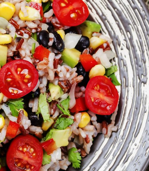 Five-minute burrito bowl topped with cherry tomatoes, avocado and cheese.