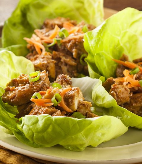 A plate of three chicken lettuce wraps.