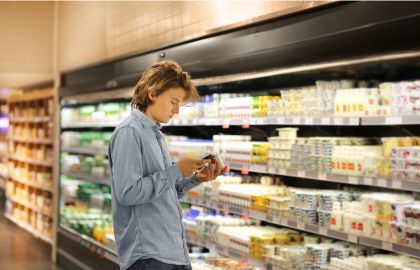 ollege student reading labels on a food product while grocery shopping.