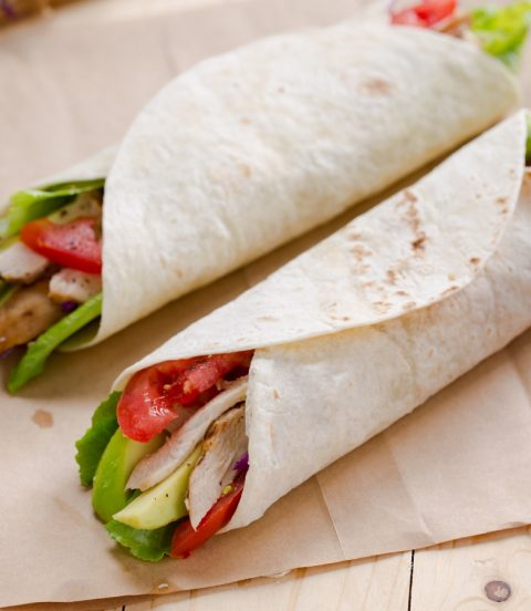 Two tricked out turkey wraps with turkey, avocado, lettuce and tomato.
