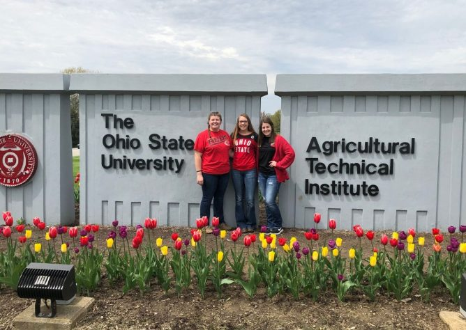 Three OSU ATI students smile in front of the campus sign.