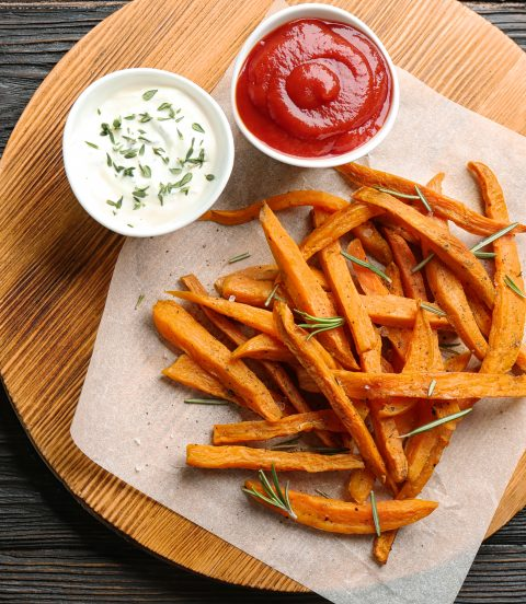 Homemade sweet potato fries with ketchup and mayo for dipping.